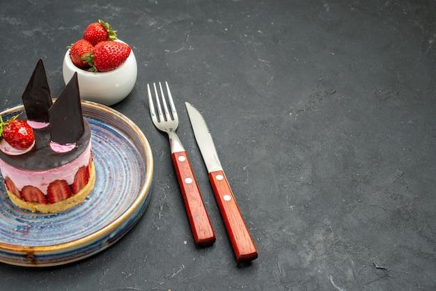 Delicioso cheesecake de frente com morango e chocolate na tigela do prato com garfo de morangos