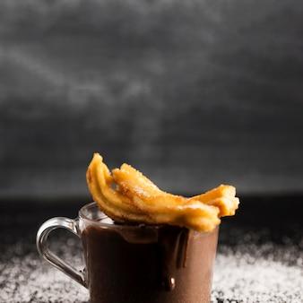 Delicioso chocolate derretido em um copo com churros