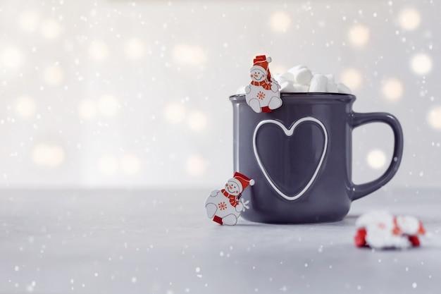Delicioso chocolate quente com marshmallow e pequenos snowmans em fundo de pedra cinza