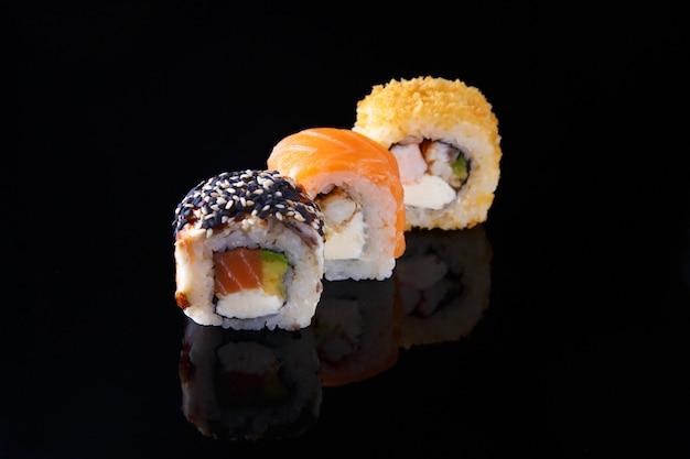 Delicioso conjunto de sushi roll com peixe em um fundo preto com reflexão menu e restaurante