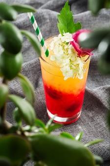 Delicioso coquetel com suco de laranja e red tequila sunrise, cubos de gelo em um copo em cinza