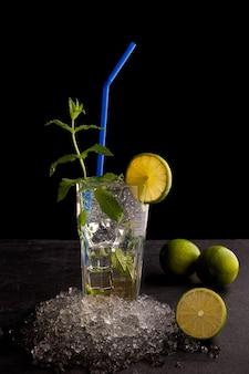 Delicioso coquetel de menta refrescante chamado mojito com rum e limão, bebida gelada ou bebida com gelo na parede preta