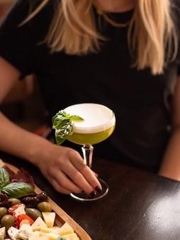 Delicioso coquetel de verão frio com limão, hortelã e gelo em um copo com gotas. coquetel de álcool multicolorido no bar.