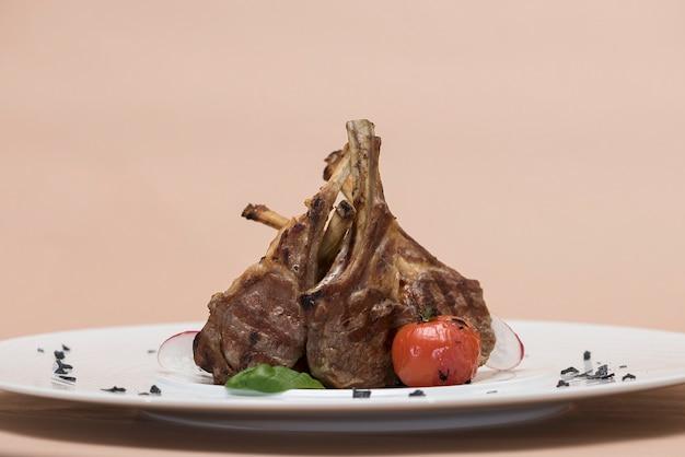 Delicioso costelas de cordeiro grelhado, com tomate grill e decorado com rabanete, espinafre, folha verde
