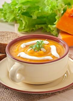 Delicioso creme de sopa de abóbora em uma tigela na mesa de madeira