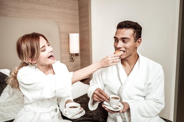 Delicioso croissant fresco. namorada loira dando ao seu homem um delicioso croissant fresco tomando café da manhã na cama
