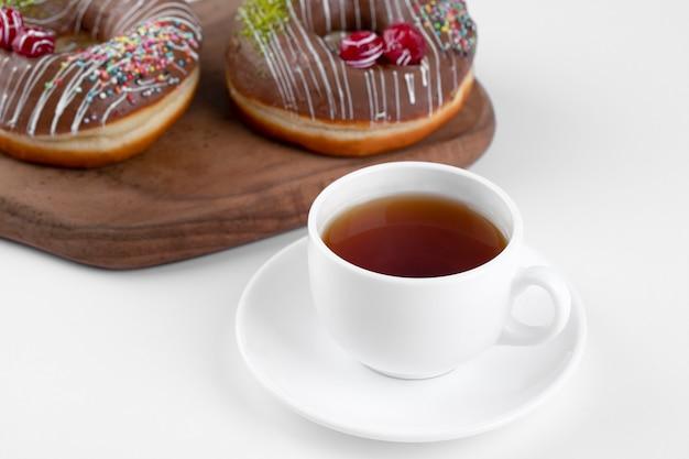 Delicioso donut de chocolate fresco com uma xícara de chá em uma tábua de madeira.