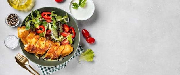 Delicioso e crocante bacalhau à milanesa com salada no prato