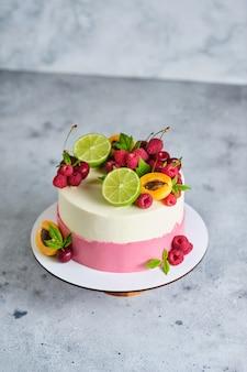 Delicioso e lindo bolo artesanal. confeitaria para o feriado. a sobremesa é decorada com framboesas frescas, cerejas, limas e damascos.