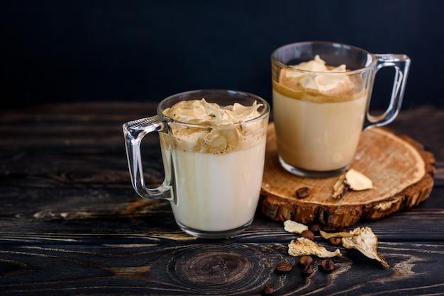 Delicioso e perfumado dalgona café em copos de vidro, paus de canela, cogumelos secos, uma colher de café instantâneo, açúcar.