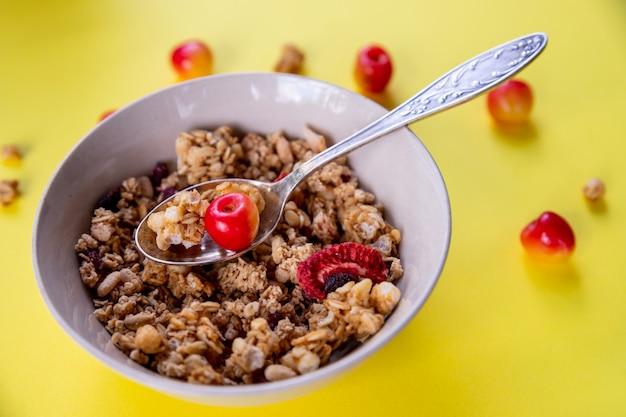 Delicioso e saudável café da manhã com cereais integrais, com muitas frutas secas, nozes, grãos e cerejas frescas