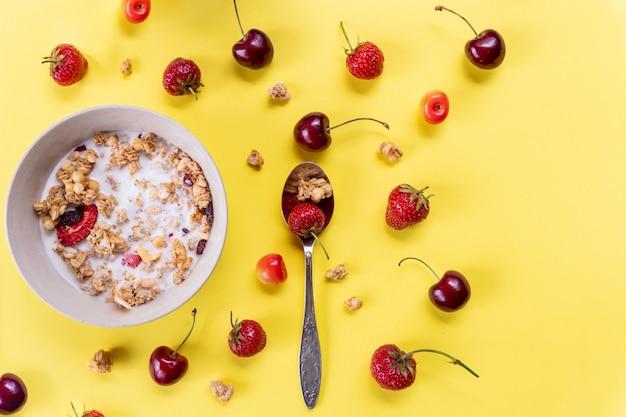 Delicioso e saudável café da manhã com cereais integrais, muitas frutas secas, nozes, grãos e cerejas frescas