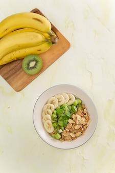 Delicioso e saudável café da manhã com leite, flocos de milho, kiwi, banana