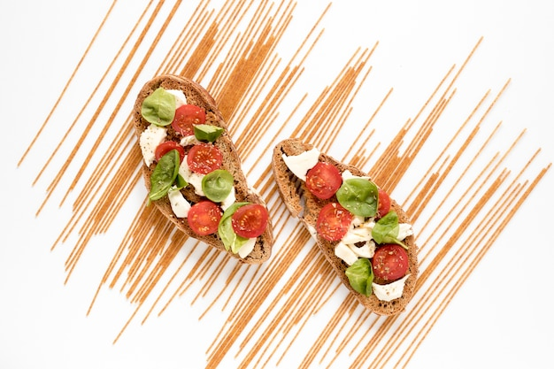 Delicioso enfeite bruschetta e macarrão espaguete cru sobre o pano de fundo branco