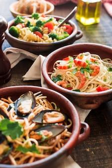 Delicioso espaguete com camarões e mexilhões na louça de barro