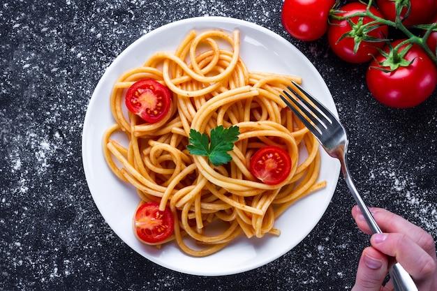 Delicioso espaguete com salsa, tomate cereja e molho de tomate em um prato. comida italiana e massas. vista do topo