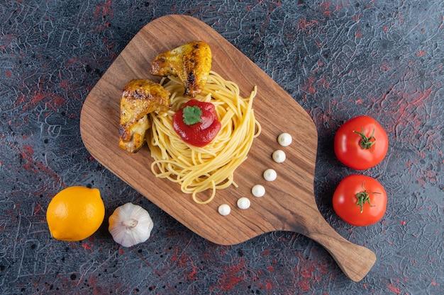 Delicioso espaguete e asas de frango na placa de madeira com legumes.
