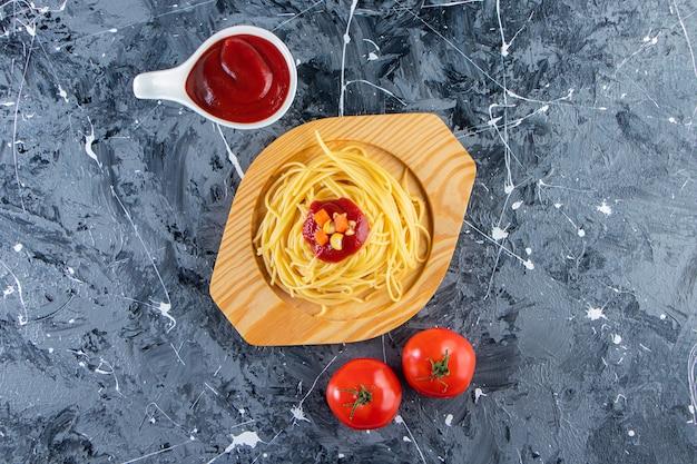 Delicioso espaguete na placa de madeira com tomate fresco e molho de tomate.
