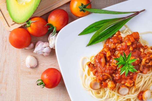 Delicioso espaguete servido em um prato branco na mesa de madeira