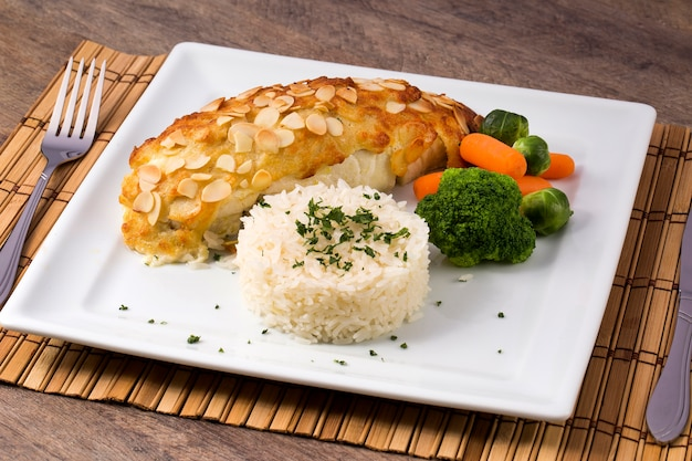 Delicioso filé de peixe grelhado saudável servido em uma travessa com uma colorida salada fresca para um saboroso jantar de frutos do mar.