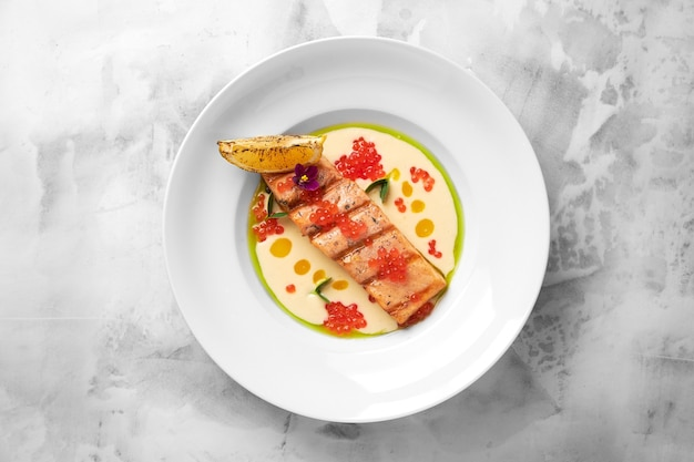 Delicioso filé de salmão grelhado com molho cremoso em um prato branco sobre fundo claro. frutos do mar saborosos