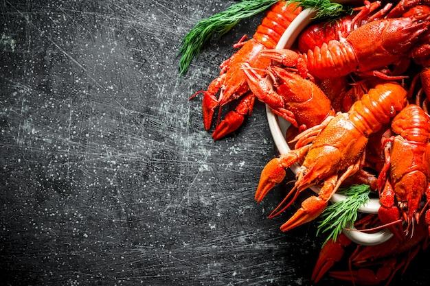 Delicioso fragrante lagostim cozido com endro na mesa rústica escura.