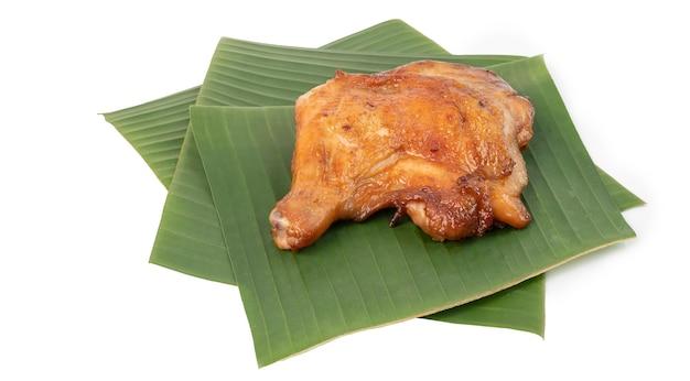 Delicioso frango grelhado em folhas de bananeira verdes frescas para prato isolado no fundo branco