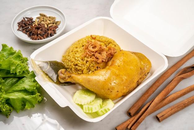 Delicioso frango picante biryani embalado em pacote de plástico, conceito de entrega de comida de arroz com curry amarelo frango biryani.