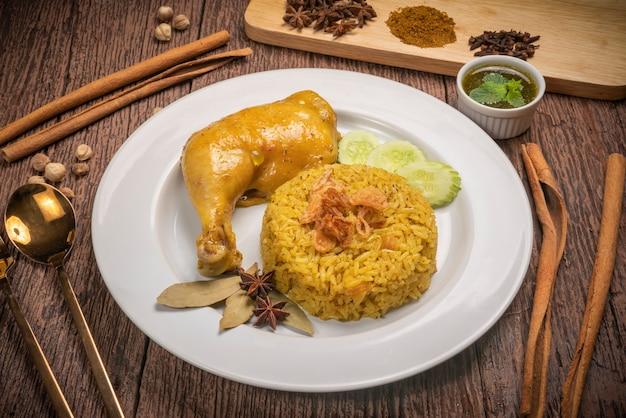 Delicioso frango picante biryani na mesa de madeira rústica, estilo tailandês de frango biryani.