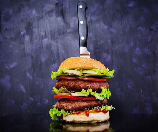 Delicioso hambúrguer artesanal no escuro. fechar vista