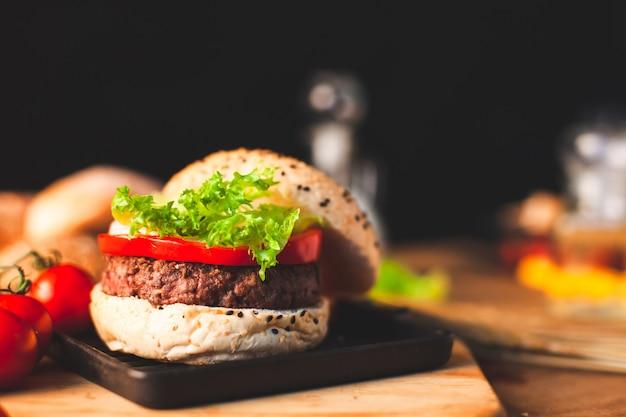 Delicioso hambúrguer caseiro com legumes frescos na cozinha