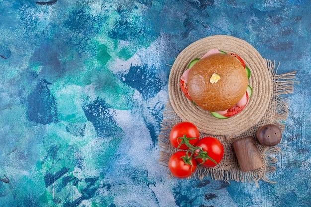 Delicioso hambúrguer caseiro com tomates frescos na superfície azul.