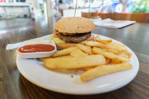 Delicioso hambúrguer caseiro de carne servido com batata frita na mesa de madeira