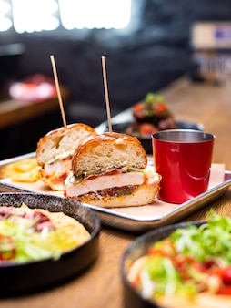 Delicioso hambúrguer caseiro grelhado com carne, queijo, bacon e molho na mesa de madeira com espaço de cópia. mãos segurando hambúrgueres com batatas fritas e cerveja. grupo de amigos comendo fast food