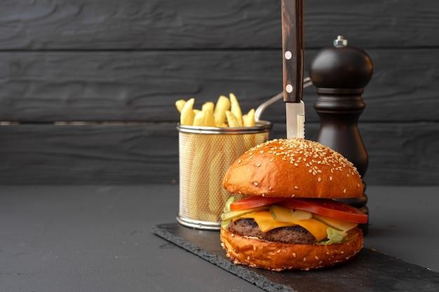 Delicioso hambúrguer com batatas fritas em uma placa de madeira contra preto