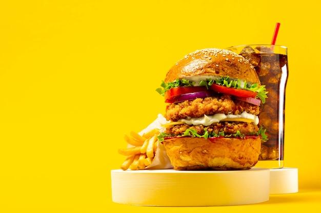 Delicioso hambúrguer com cola e batata frita em um fundo amarelo
