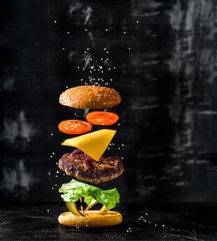Delicioso hambúrguer com ingredientes a voar em fundo escuro