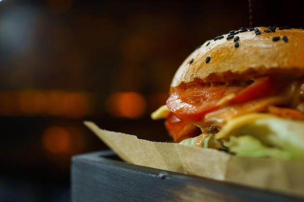 Delicioso hambúrguer com pãezinhos brancos crocantes com deliciosa costeleta de frango com tomates frescos e pepinos com queijo derretido e molho com batatas assadas em uma placa de madeira em um café. fechar-se