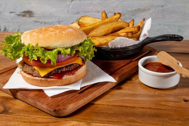 Delicioso hambúrguer com queijo cheddar, alface, tomate, rodelas de cebola roxa e bacon grelhado no pão caseiro acompanhado de espetaculares batatas rústicas e molho barbecue caseiro.