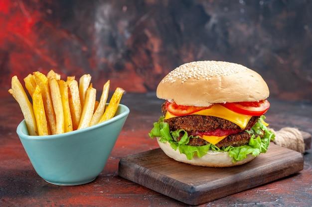 Delicioso hambúrguer de carne com batata frita em fundo escuro de vista frontal