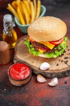 Delicioso hambúrguer de carne com batata frita em piso escuro de frente