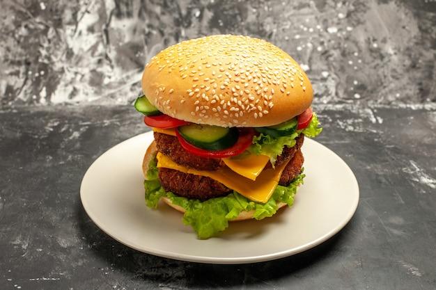 Delicioso hambúrguer de carne com legumes em um sanduíche de pão de fast-food de superfície escura com vista frontal