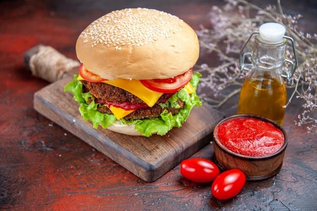 Delicioso hambúrguer de carne com queijo em um fundo escuro de vista frontal