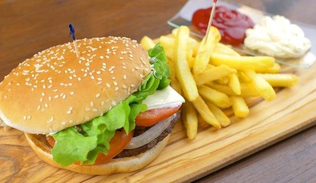 Delicioso hambúrguer grelhado com batata frita na placa de madeira