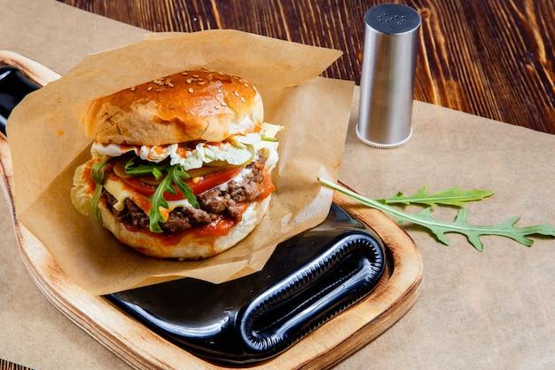 Delicioso hambúrguer na mesa de madeira
