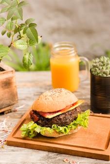 Delicioso hambúrguer na tábua de cortar servido com jarra de suco na mesa de madeira