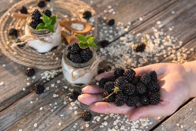Delicioso iogurte fresco no café da manhã com amoras adicionadas. um punhado de amoras silvestres está na palma da sua mão.