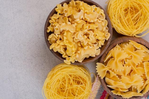 Delicioso macarrão cru e vermicelli em tigelas de madeira