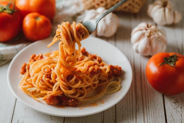 Delicioso macarrão espaguete caseiro com molho de tomate e carne picada servido em um prato branco com ingredientes em uma superfície de madeira branca