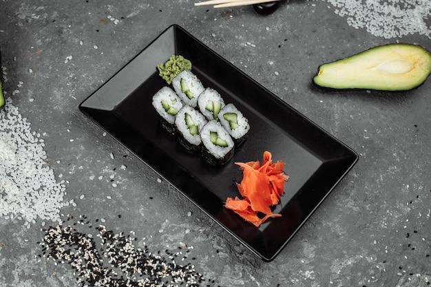 Delicioso maki suculento e de dar água na boca com sushi de pepino em um fundo cinza